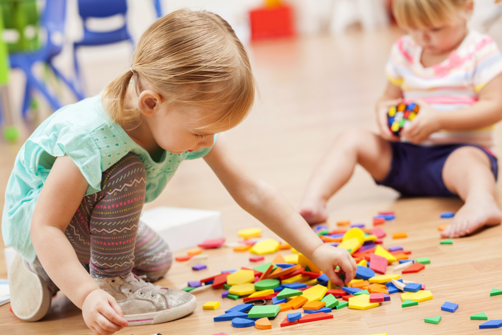 Toddler girls playing with puzzle pieces in a preschool classroom