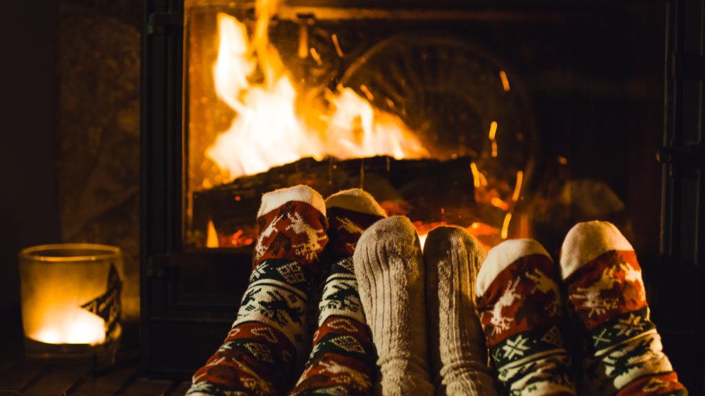 Closeup of three people feet by fireplace