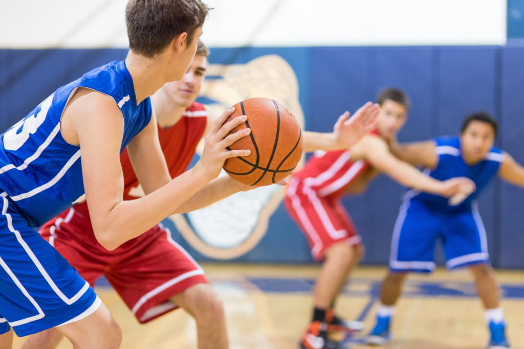 A high school basketball player holds the ball carefully outside the key as he's guarded. He's trying to decide who to pass to...