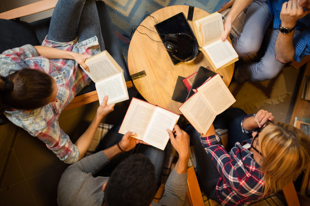 people sitting around table with books opened