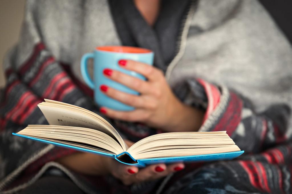 Woman holding a coffee mug and book