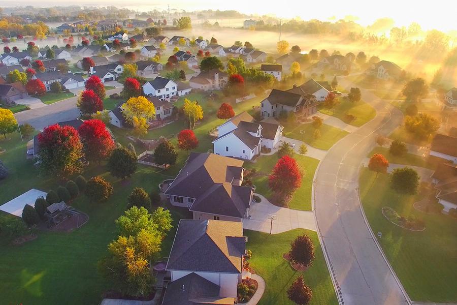 Spectacular sunbeams through fog in autumn neighborhood, aerial view.