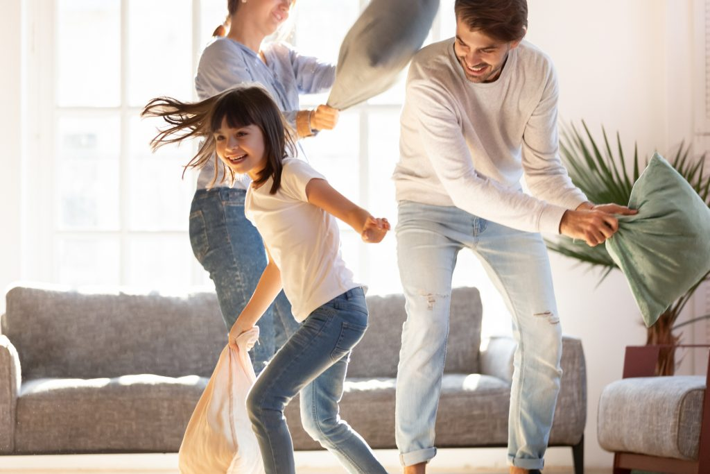 Playful parents engaged in pillow fight with little daughter