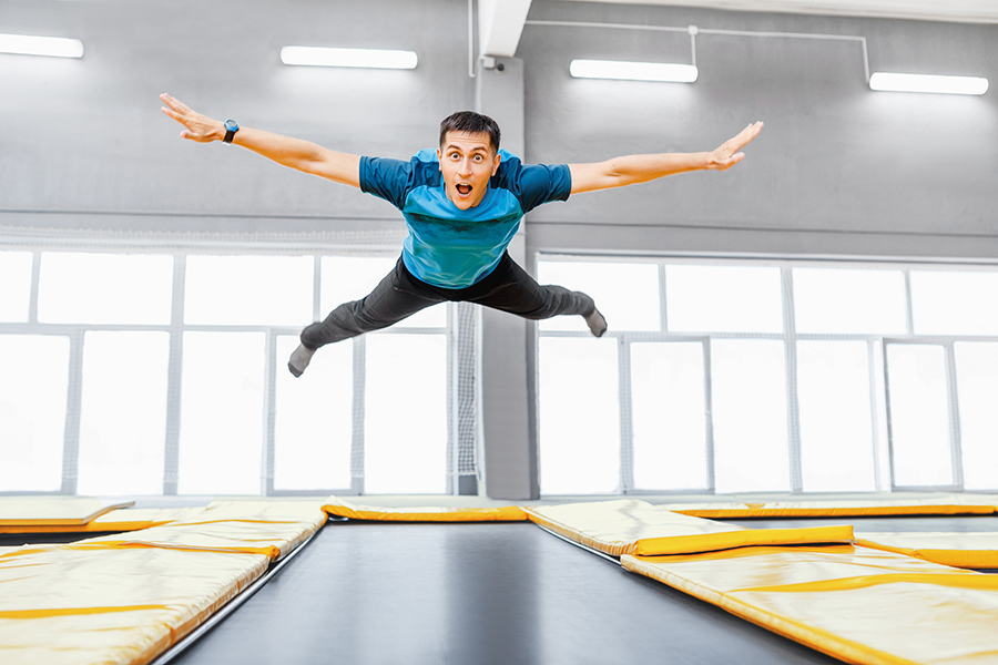a young man jumping on a trampoline