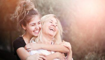 Daughter hugging mom around the neck