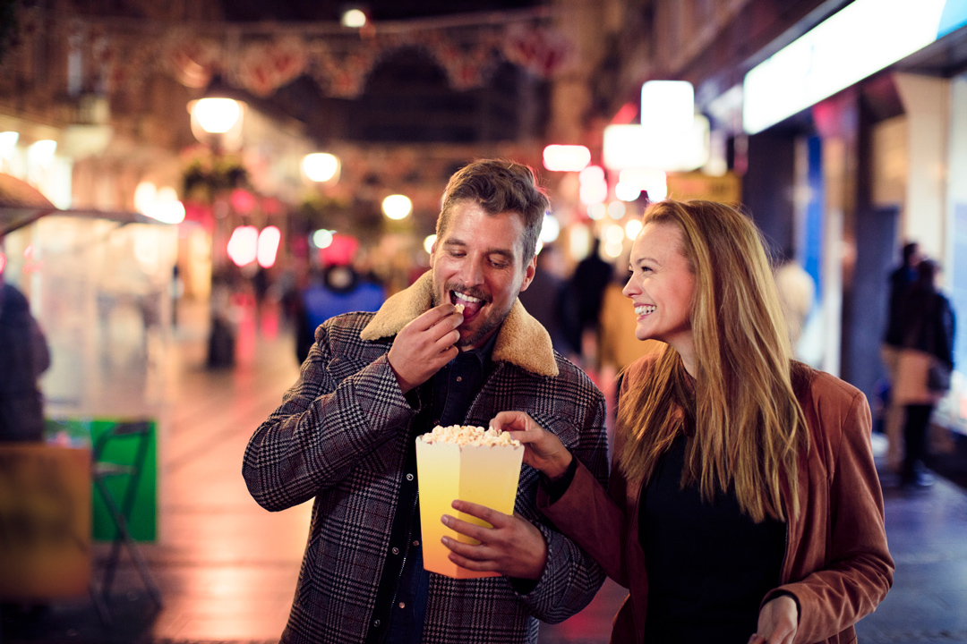 Close up of a young couple shopping in the city at night
